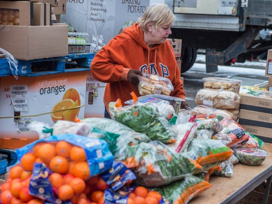 Food bank volunteer Joyce Garrison sets out fresh produce for for distrubtion Friday morning donated by Firekeeper Casino.