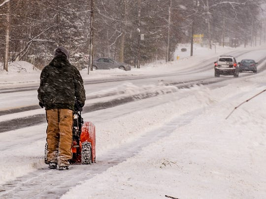 Maintence worker uses snow blower to clear off sidewalks along Capital Ave SW as as a result of a Jan. 12 snowfall.
