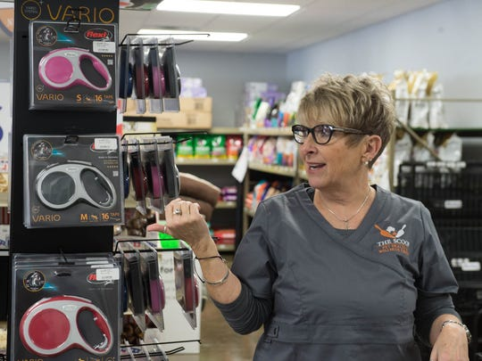 Irena Rees shows some of the dog leashes  at The Scoop, a pet health and wellness center, opened last month in Battle Creek.