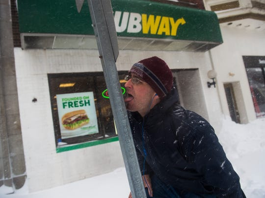 Peter Myers, of Hanover, tests to see if his tongue would freeze to a steel post Saturday while shoveling outside a Subway restaurant in downtown Hanover.