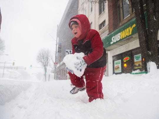 Brandon Shonyo Jr., 5, of Hanover, lifts a giant snowball to throw at his dad Saturday Jan. 23, 2016 in downtown Hanover, Pa.