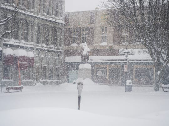 A parking meter is buried in snow as it continues to fall in Center Square, Hanover, Pa. on Saturday Jan. 23, 2016.
