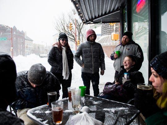 A group of patrons enjoy drinks outside in Center Square at Miscreation Brewing as a few businesses were open downtown Hanover on Saturday Jan. 23, 2016.
