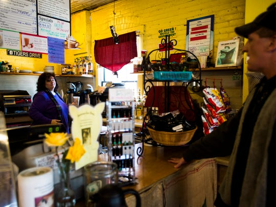 Merlin's Coffee owner Donna Burns, left, prepares coffee for regular customer Jeremy Siedenstricker, right, on Wednesday in Hanover.