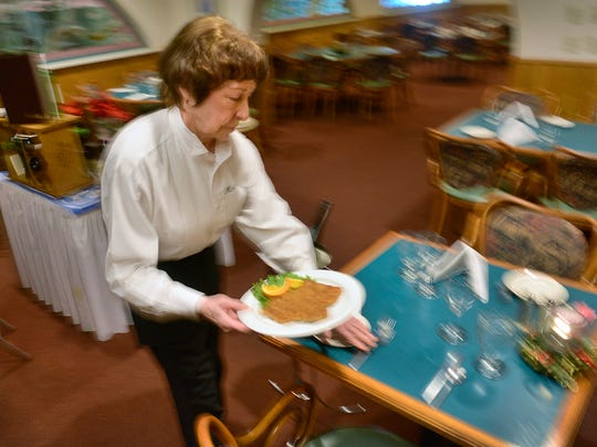 At 81, Michael's restaurant server Clara Riley carries a plate of wienerschnitzel to a table Thursday, Feb. 4 at the restaurant which specializes in Austrian cuisine. She has been waitressing for over 50 years and doesn't have any plans to stop now.