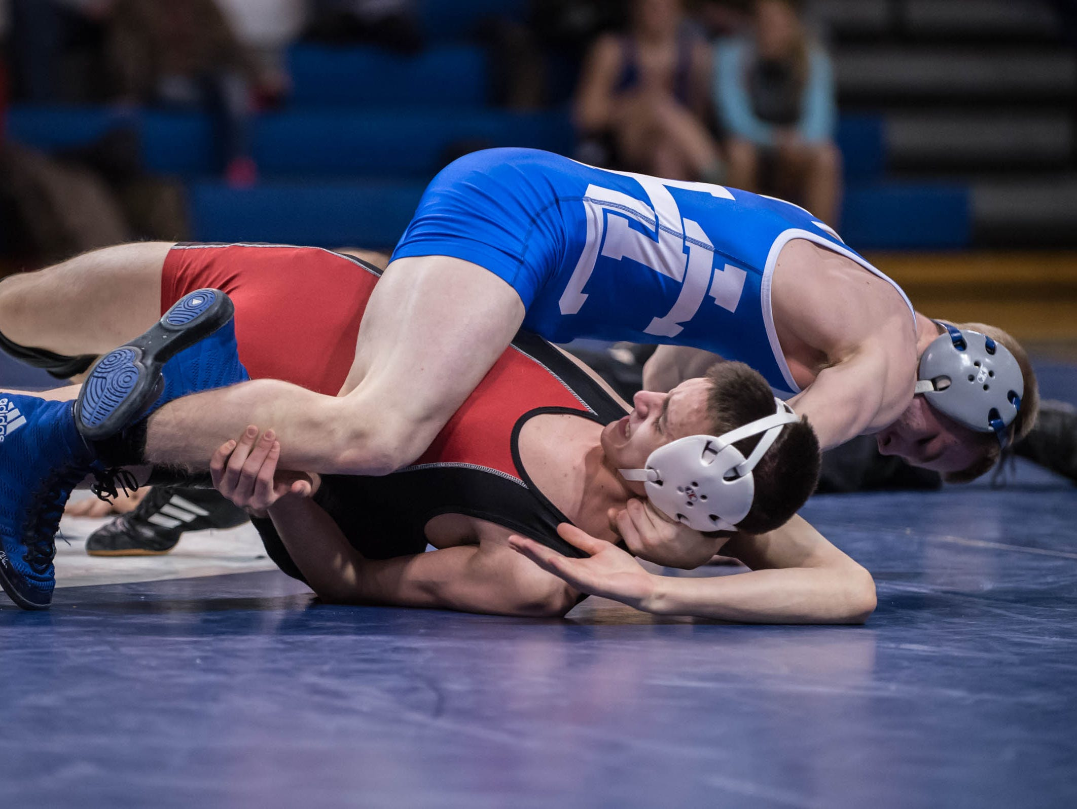 Harper Creek's Ethan Bishop (top) wrestles Marshall's Willie Couch in 125 pound weight class during Wednesday's district match.