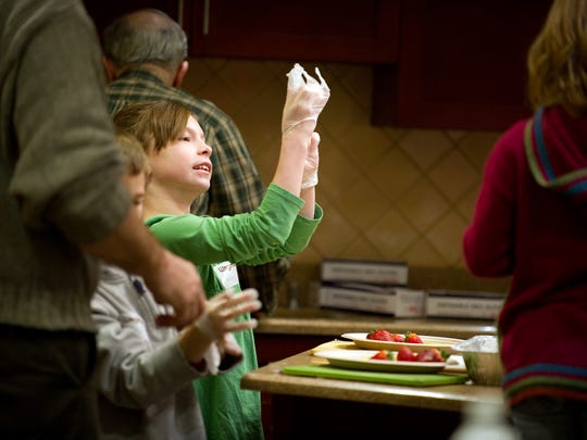 Ashley Thrash of Henrietta puts on disposable gloves in preparation for cutting her fruit and vegetables during a 2010 Kids in the Kitchen program at the Rochester Menu Cooking School in the Pittsford Wegmans.