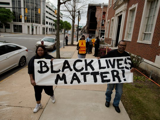 Aretha Vettis, left, and Tom Simon hold a sign during a protest on Thursday, March 10, 2016, of the cities handling and response to the police involved shooting of Greg Gunn in Montgomery, Ala. Greg Gunn, a black male, was fatally shot by Montgomery Police Officer Aaron C. Smith, a white male, on Thursday, Feb. 25, 2016. Aaron C. Smith has been arrested for murder in relation to the shooting.
