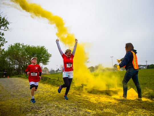 Runners power through a yellow cloud during the second