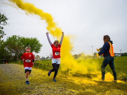 Runners power through a yellow cloud during the second annual Hanover YWCA Race Against Racism color run at Moul Field on Saturday April 30, 2016.