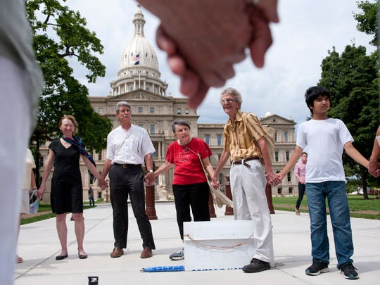 Margaret Kingsbury, in red, leads a moment of silence in front of the Capitol on Friday, Aug. 19, 2016. A handful of Lansing residents have been in front of the Capitol every Friday since the Friday after Sept. 11, 2001 to protest in favor of peace.