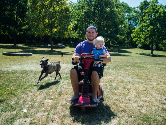 Breighton Engelhart holds his 16-month-old son, Daniel, while using a motorized scooter to get around his home in East Berlin.