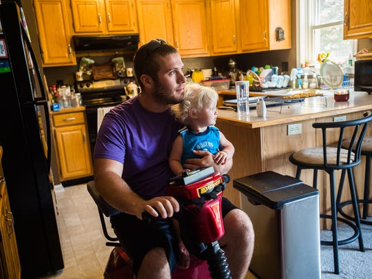 Breighton Engelhart holds his 16 month-old son, Daniel, while using a motorized scooter to get around his home in East Berlin. The Father and son were in a car crash in Oxford Township in June that left Breighton with serious injuries.