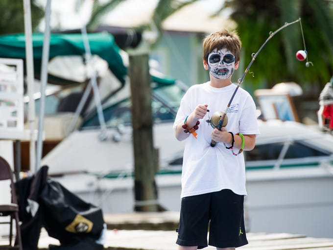 Mason Martin, 7, reels in his fishing pole during the