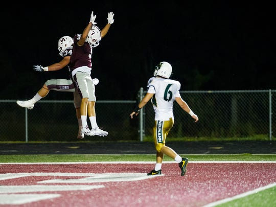 First Baptist Academy's Joe Sparacio(34) celebrates a touchdown with Drake Woods(3) during a game against St. John Neumann in Naples, Fla., on Friday, Oct. 21, 2016.