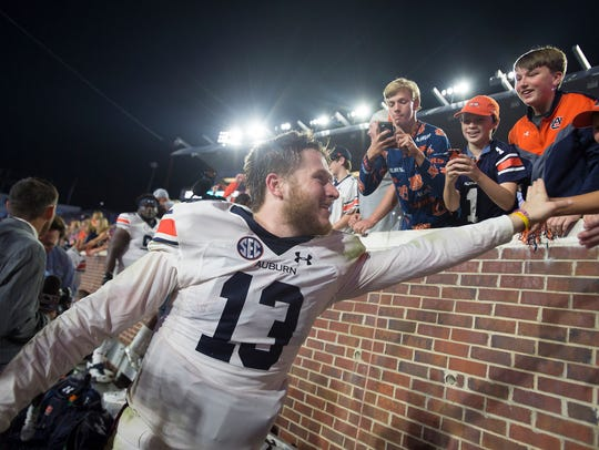 Auburn quarterback Sean White (13) celebrates with