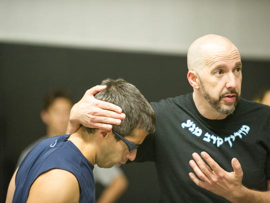 Krav Maga owner and instructor Tim Kubit, demonstrates a tactical defense move against student Marco Mennucci, 36, of Livonia during a recenty class.