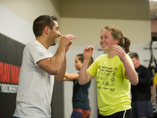Maddie Hager, 17, of Brighton shares a laugh with fellow student Alex Hinkley, 30 of Spencerport,during a recent Krav Maga class at the school in Henrietta.
