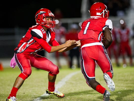 Immokalee High School's Rj Rosales hands off the ball to Charles Toombs during a game against Dunbar High School in Fort Myers, Fla., on Monday, Oct. 31, 2016.