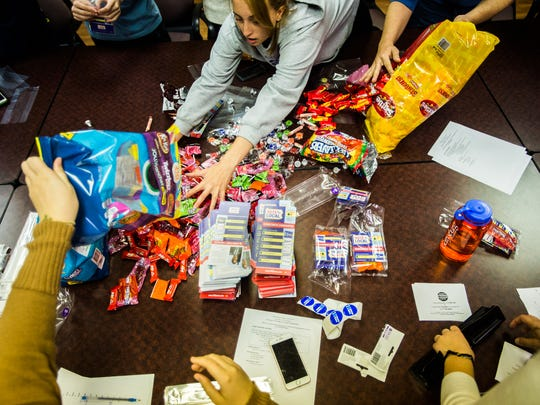 Gettysburg College sophomore Tess Mistretta, top, spreads out some candy Nov. 2, 2016 while working with fellow student members of the Gettysburg College Democrats on packaging voting reminders with treats the group plans to hand out to registered Democrats on campus before Nov. 8.