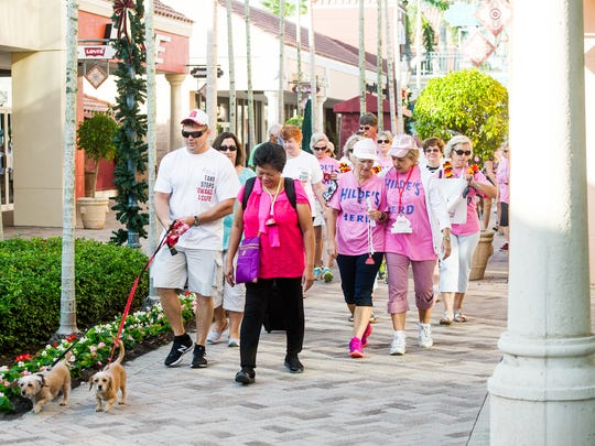 People walk past different outlet stores during a walk for ALS at the Miromar Outlets in Estero, Fla., on Saturday, Nov. 5, 2016. ALS, also known as Lou Gehrig's Disease, progressively paralyzes its victims, attacking nerve cells and pathways in the brain or spinal cord, taking away their ability to walk, talk, eat and eventually breathe.