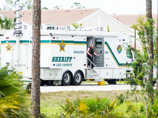 An officer leaves a Lee County Sheriff's Office communications command vehicle at the scene of an officer-involved shooting near an Interstate 75 off ramp at Corkscrew Road in Estero, Fla., on Monday, Nov. 14, 2016.