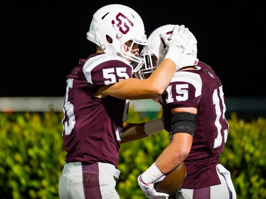 First Baptist Academy's Jayce Howell (15) celebrates with his teammate Daniel Marquina (55) during a game against St. John Neumann in Naples on Friday, Oct. 21, 2016.