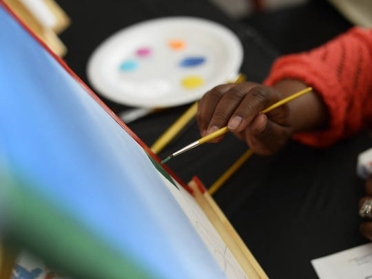 Sherry Roland of York paints during a sip and paint night Friday, December 18, 2015.