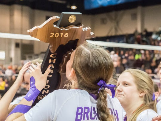 Bronson players take turns kissing their trophy at center court after winning the 2016 Class C State Volleyball Championship at Kellogg Arena on Saturday.