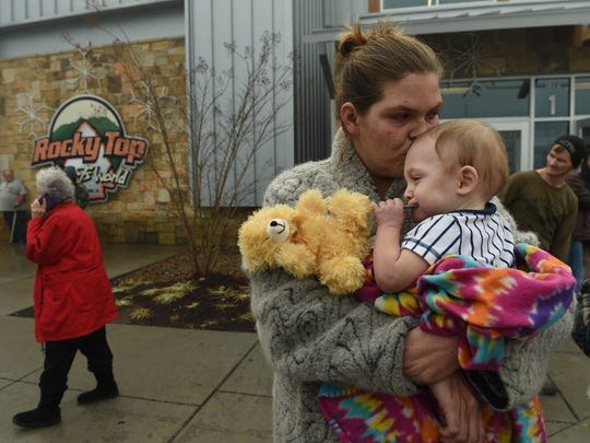Shari Deason holds 14 month-old son William outside of the Rocky Top Sports Center, serving as a Red Cross shelter, next door to the TEMA command center at Gatlinburg-Pittman High School in Gatlinburg on Tuesday, Nov. 29, 2016. More than 2,000 people have checked in to various shelters. Deason said she had to leave all of her belongings behind when evacuated from a hotel overnight.