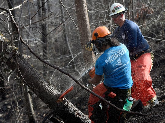 Volunteers, left to right, George Hernandez Mejia and Bennie Sims, with All Hands and Reach Out Worldwide begin to help clear trees of the Thompson family home Friday, Dec. 9, 2016, in Gatlinburg, Tenn.