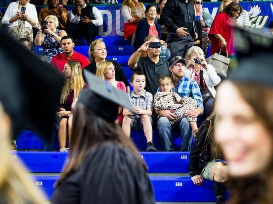 Students line up and wait for their names to be called as friends and family watch on and take photos during the commencement of the Fall 2016 class of FGCU at Alico Arena in Fort Myers, Fla., on Sunday, Dec. 11, 2016. FGCU has awarded more than 23,000 degrees since fall 1997.