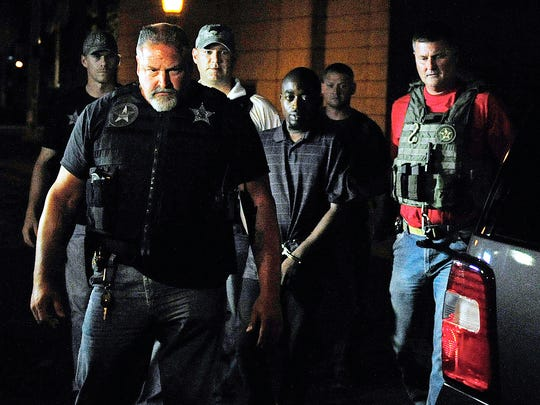 A murder suspect who was on the most-wanted list is escorted in May 2014 by U.S. marshals and Lee County sheriff's deputies during a perp walk near the Old Lee County Courthouse in Fort Myers.