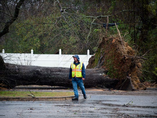 Workers clear a tree that fell on a street North Broad Street in Wetumpka, Ala., during a storm on Saturday, Jan. 21, 2017.