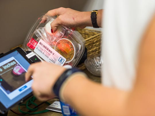A customer uses a payment system to buy food during the lunch hour at CSI Enterprises Inc offices in Bonita Springs, Fla., on Monday, Jan. 23, 2017. CSI invested in a company that came up with an idea for the a healthy workplace market and developed a payment system for the market. The company goes by the name Delicious, Nutritious Markets.