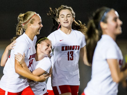 North Fort Myers High School's Emilee Hauser(18) embraces her teammate Macey Earhart(5) after a goal against Naples High School in North Fort Myers, Fla., on Thursday, Jan. 26, 2016.