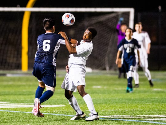 Estero High School's Bryan Guevara(6) goes up against