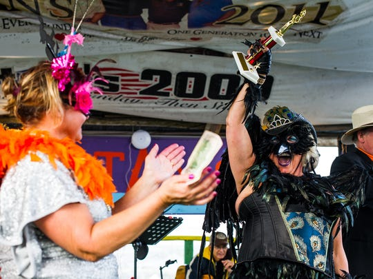 Lisa Bacewicz holds her trophy after winning the Queen Buzzard Lope dance contest during the 33rd Annual Mullet Festival in Goodland, Fla., on Sunday, Jan. 29, 2017.