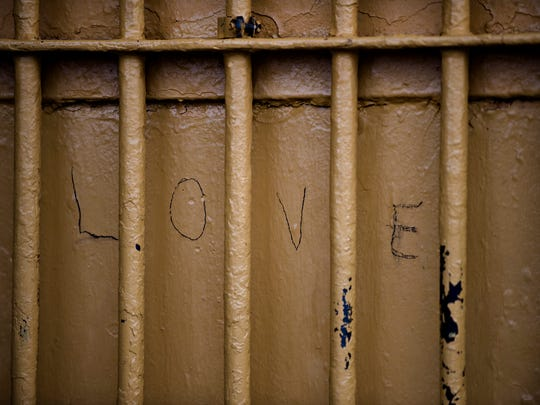 "The word ""Love"" is carved into a prison door leading"