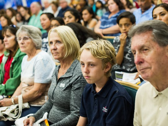 Bradley Walters, an eighth grade student at Bonita Charter School, center, sits and watches a tour video with Donald Harris and his wife, Terry, during a parent information night on the new Bonita Springs High School on Tuesday, Feb. 7.