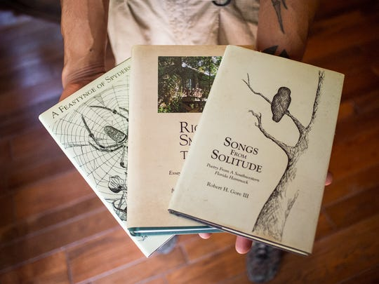 Alex Rodriguez holds out some of Bob Gore's published books while at his house in Golden Gate Estates on Sunday, Feb. 26, 2017. Gore died in February, leaving questions about the fate of his life's work, a wildlife sanctuary he created parcel by parcel with his own money and used to educate schoolkids about nature and host folk music festivals.