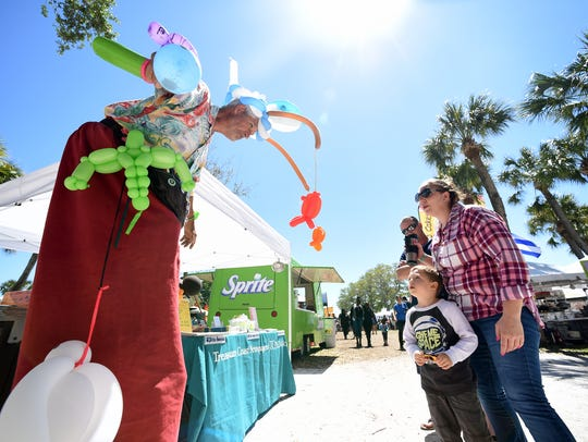 """Jeff """"The Balloon Guy"""" Dorian jokes with Robert Campbell III, 4, and Krystle Holmes, both of Fort Pierce at last year's Sandy Shoes Seafood Festival at Veteran's Memorial Park in downtown Fort Pierce. This year's festival has added craft brews and will be 10 a.m. to 8 p.m. Saturday."""