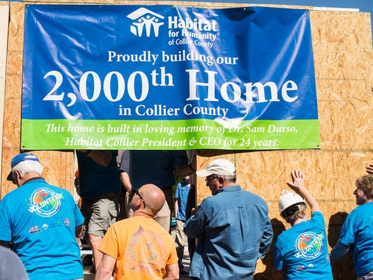 People raise one of the walls for a new home during an event celebrating the 2000th home built by Habitat for Humanity of Collier County while in Naples Manor on Saturday, March 18, 2017. Volunteers, donors, staff, neighbors and the home's future owners celebrated the milestone and the legacy of Habitat Collier's late CEO, Dr. Sam Durso, who funded the construction of the home.
