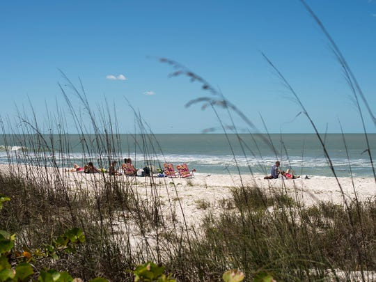"""People soak up the sun near """"No Trespassing"""" signs that stand in front of homes on the Little Hickory Island area of Bonita Springs on Friday, April 7."""