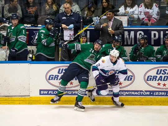Florida Everglades forward Dalton Smith(24) gets checked into the bench by Orlando's Jeff King(2) during Game 1 of the Kelly Cup Playoffs against the Orlando Solar Bears at Germain Arena in Fort Myers, Fla., on Wednesday, April 12, 2017.