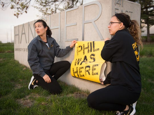 "University of Iowa students Erin Glenn and Samantha Klemm tag the campus Tuesday with signs reading ""Phil was here"" for the UI Foundation's annual celebration of philanthropy."