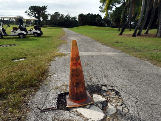 An orange cone alerts golfers of a pot hole at the