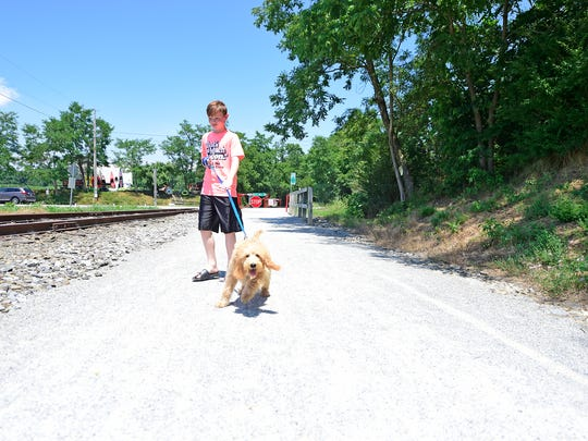 Eleven-year-old Rylan March of North Codorus Township walks his dog Rufus, a five-month-old mini labradoodle, on the Heritage Rail Trail.