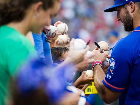 Tim Tebow signs memorabilia before a Fort Myers Miracle