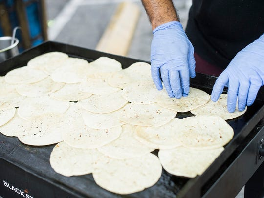 Alan Romero, 21, grills up some tortillas outside of